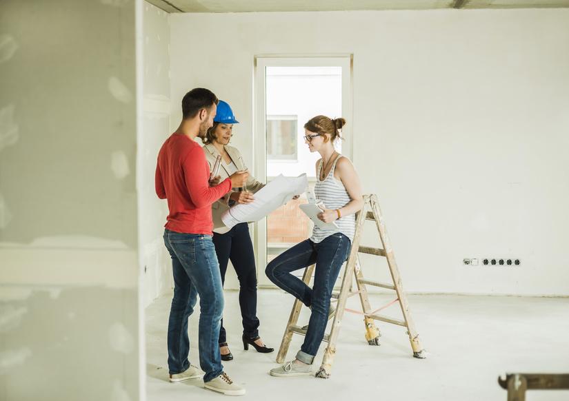 appartement - architecte montrant un plan à un jeune couple